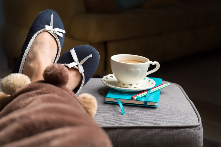 female legs covered with warm blanket, relax at home